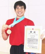 インターハイ優勝のメダルと賞状を手に笑顔の長﨑選手=四日市市の相好体操クラブで
